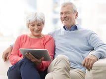 Pares mayores con la tableta de Digitaces Imagen de archivo libre de regalías