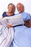 Pares mayores con la tableta y el periódico en cama Imágenes de archivo libres de regalías