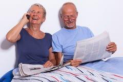 Pares mayores con la tableta y el periódico en cama Foto de archivo libre de regalías
