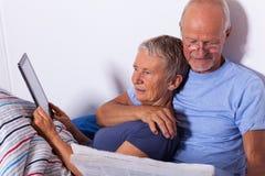 Pares mayores con la tableta y el periódico en cama Imagen de archivo