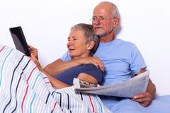Pares mayores con la tableta y el periódico en cama Imagen de archivo libre de regalías