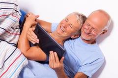 Pares mayores con la tableta y el periódico en cama Fotos de archivo