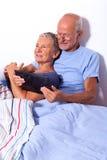 Pares mayores con la tableta y el periódico en cama Fotos de archivo libres de regalías