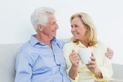 Pares mayores con la taza de café que se sienta en el sofá Fotografía de archivo