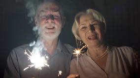 Pares mayores con las bengalas que celebran Familia feliz que lleva a cabo las luces de Bengala que disfrutan de Nochebuena almacen de video