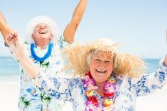 Pares mayores con los brazos para arriba en la playa Foto de archivo libre de regalías