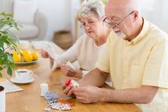 Pares mayores con los problemas de salud que leen prospectos de drogas imágenes de archivo libres de regalías