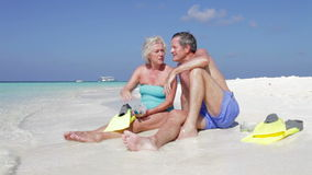 Pares mayores con los tubos respiradores que disfrutan de día de fiesta de la playa Imagenes de archivo