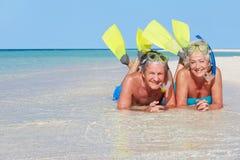 Pares mayores con los tubos respiradores que disfrutan de día de fiesta de la playa Fotografía de archivo