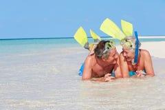 Pares mayores con los tubos respiradores que disfrutan de día de fiesta de la playa Imagen de archivo