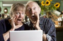Pares mayores dados una sacudida eléctrica con un ordenador portátil Imagenes de archivo