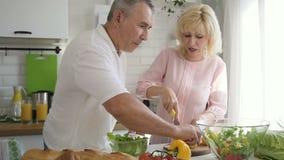Pares mayores de la familia que cocinan la ensalada para el almuerzo junta en cocina almacen de metraje de vídeo