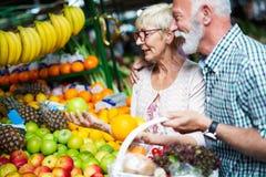 Pares mayores de la familia que eligen la bio fruta y verdura de la comida en el mercado durante compras semanales imagenes de archivo
