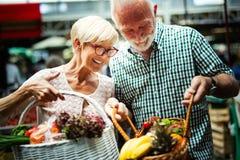 Pares mayores de la familia que eligen la bio fruta y verdura de la comida en el mercado durante compras semanales imagen de archivo libre de regalías