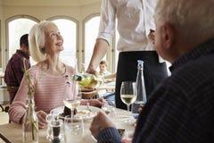 Pares mayores de Serving Wine To del camarero en restaurante Imagen de archivo libre de regalías