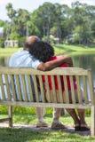 Pares mayores del afroamericano en banco de parque Foto de archivo