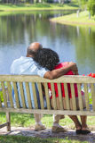 Pares mayores del afroamericano que se sientan en banco Imágenes de archivo libres de regalías