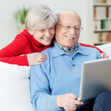 Pares mayores divertidos usando un ordenador portátil fotos de archivo