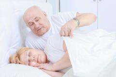 Pares mayores dormidos en cama Fotos de archivo libres de regalías