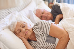Pares mayores dormidos en su cama en casa Imágenes de archivo libres de regalías