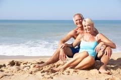 Pares mayores el día de fiesta de la playa Imagen de archivo