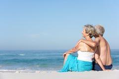 Pares mayores el el día de fiesta que se sienta en la playa de Sandy Fotografía de archivo