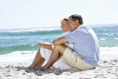 Pares mayores el el día de fiesta que se sienta en la playa de Sandy fotos de archivo