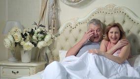 Pares mayores emocionados que ríen junto en cama almacen de video