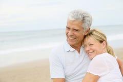 Pares mayores en amor en el abarcamiento de la playa Fotos de archivo libres de regalías