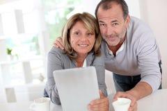 Pares mayores en casa que beben el café y que usan la tableta Fotografía de archivo