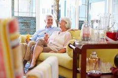 Pares mayores en casa que se relajan en salón con las bebidas frías Imagenes de archivo
