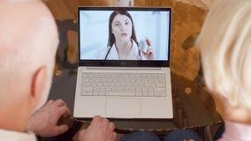 Pares mayores en casa que tienen consulta video de la charla vía llamada del app del mensajero en el ordenador portátil con el mé almacen de video