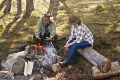 Pares mayores en el bosque que se sienta por un fuego del campo fotografía de archivo libre de regalías