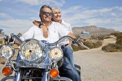 Pares mayores en el camino del desierto que se sienta en la motocicleta Imagenes de archivo