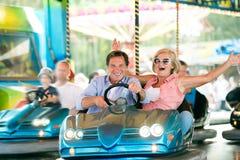 Pares mayores en el coche de parachoques en la feria de diversión foto de archivo
