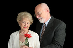 Pares mayores en el negro - gesto romántico Foto de archivo