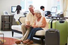 Pares mayores en el pasillo del hotel que mira la tableta de Digitaces Imagenes de archivo