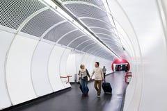 Pares mayores en el vestíbulo del subterráneo que tira del equipaje de la carretilla Foto de archivo