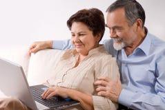 Pares mayores en la computadora portátil foto de archivo