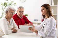 Pares mayores en la consulta con un doctor fotos de archivo