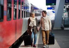 Pares mayores en la estación de tren que tira del equipaje de la carretilla Fotos de archivo libres de regalías