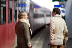 Pares mayores en la estación de tren que tira del equipaje de la carretilla Imagenes de archivo
