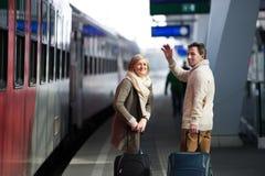 Pares mayores en la estación de tren que tira del equipaje de la carretilla, agitando Imagen de archivo libre de regalías