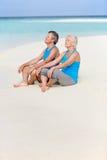 Pares mayores en la ropa de los deportes que se relaja en la playa hermosa Foto de archivo libre de regalías