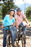 Pares mayores en paseo de la bici del país Foto de archivo libre de regalías