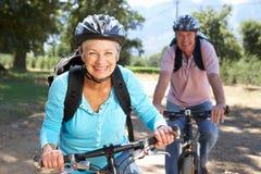 Pares mayores en paseo de la bici del país foto de archivo