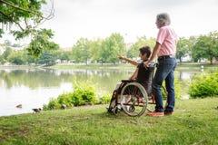 Pares mayores en silla de ruedas foto de archivo libre de regalías