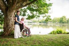 Pares mayores en silla de ruedas fotografía de archivo