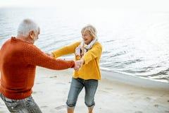 Pares mayores en su?teres en la costa foto de archivo
