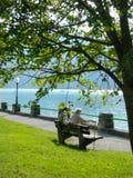 Pares mayores en un banco al lado de un lago de la montaña Foto de archivo